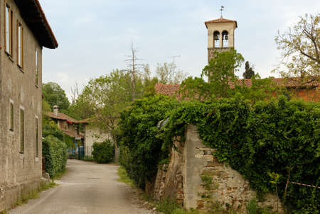 Small country road near Manzano, Friuli region, Italy, with a bell tower in the background