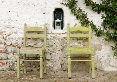 Two traditional wooden chairs against the exterior wall of a country house Reklamní fotografie - 123097404