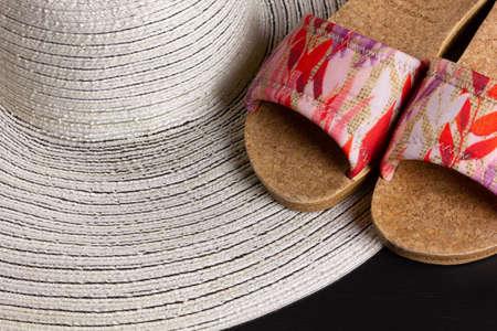 A white straw hat and womens beach sandals Reklamní fotografie