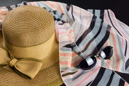 Straw hat with a big bow, a pink and black foulard and a pair of sunglasses