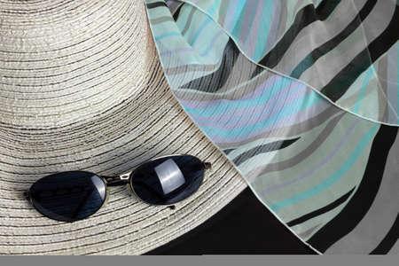 Chapeau de paille blanc, foulard noir, bleu et violet et une paire de lunettes de soleil