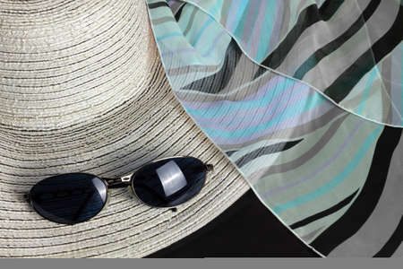 White straw hat, a black, blue and purple foulard and a pair of sunglasses Reklamní fotografie - 123097436