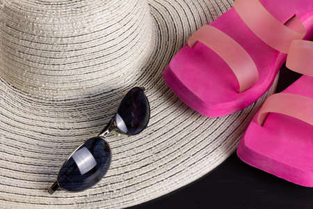 White straw hat, purple beach sandals and a pair of blue shaded sunglasses
