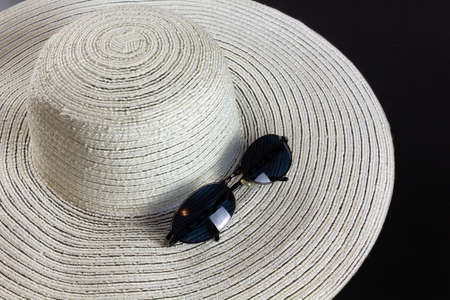 White straw hat on a dark wooden background, with a pair of  blue shaded sunglasses Reklamní fotografie - 123097439