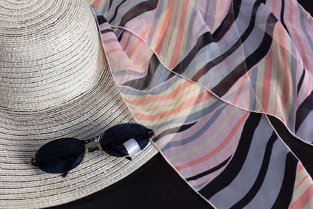 White straw hat, a pink and black foulard and a pair of blue shaded sunglasses Reklamní fotografie - 123097441