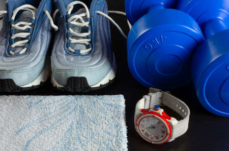 A pair of sneakers, two blue dumbbells, a towel and a modern watch on a dark wooden background Reklamní fotografie - 123097449
