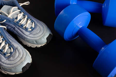 A pair of sneakers and two blue dumbbells on a dark wooden background Reklamní fotografie