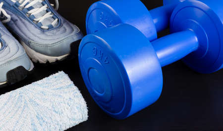 A pair of sneakers, two blue dumbbells and a towel on a dark wooden background Reklamní fotografie