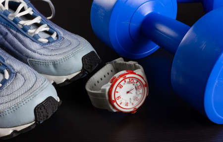 A pair of sneakers, two blue dumbbells and a modern watch on a dark wooden background Reklamní fotografie - 123097454