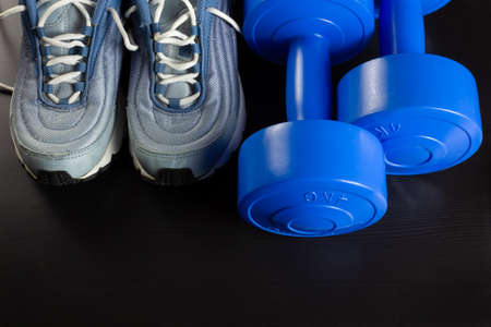 A pair of sneakers and two blue dumbbells on a dark wooden background Reklamní fotografie - 123097455
