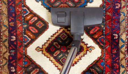 Close-up of a vacuum cleaner on an oriental carpet Reklamní fotografie - 125550264