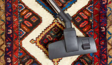 Close-up of a vacuum cleaner on an oriental carpet