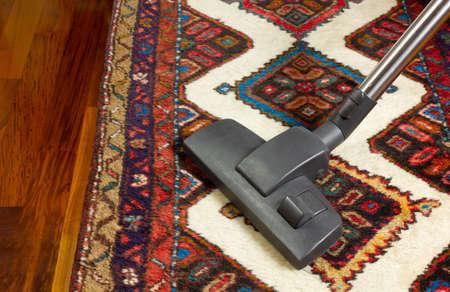 Close-up of a vacuum cleaner on an oriental carpet Reklamní fotografie - 125550271
