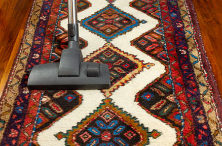 Close-up of a vacuum cleaner on an oriental carpet Reklamní fotografie - 125550275