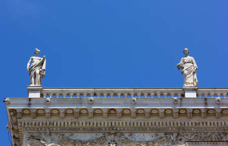 Two allegoric statues on the top of Revoltella palace in Trieste, Italy Reklamní fotografie - 125543339