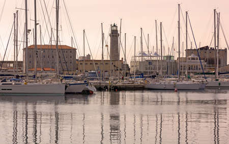 View of the Sacchetta marina at sunset, with the former Lanterna lighthouse in the background, in Trieste, Italy Reklamní fotografie - 125543340