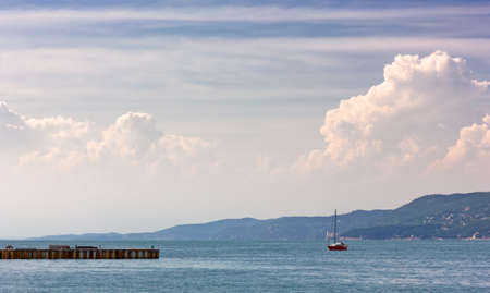 A red colored sailboat in the sea of Trieste, Italy, with the Miramare castle in the background Reklamní fotografie - 125543341