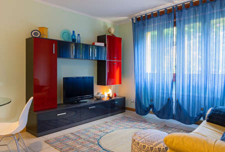 Stylish living room of a small apartment, with green walls, yellow leather sofa and a modern shiny red and black cabinet 写真素材 - 131735098