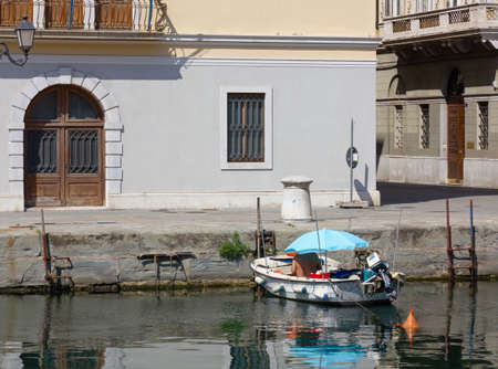 Bare chested man relaxing in a small boat, protected from the sun by a blue umbrella in the waters of the Grand Canal in Trieste, Italy