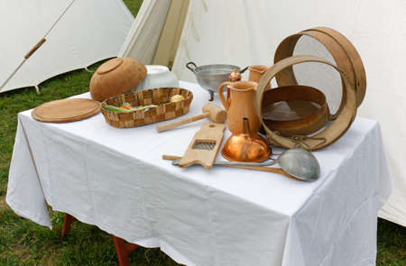 Various vintage utensils on a table during a historical reenactment Stok Fotoğraf