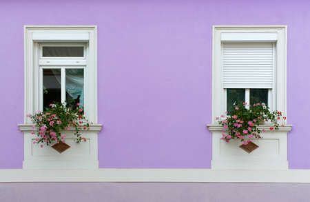 Close-up of the facade of an elegant house, with geranium flowerpots on the windowsills Stockfoto