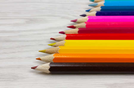 Perspective view of a series of colored pencils on a white wood background