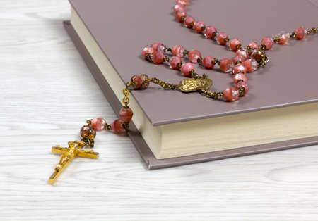 Rosary with pink colored grains lying on a book on a white wooden table