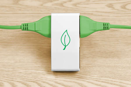 Two green cables connected to a multiple socket over a light wood background, with a leaf shape representing clean energy on the socket