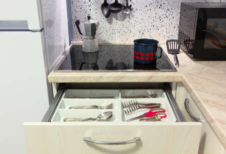 Open drawer in a modern kitchen, with a kettle and a coffee maker on the hob Stock fotó