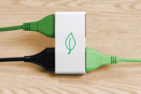 Two green cables and a black one connected to a multiple socket over a light wood background, with a leaf shape representing clean energy on the socket Archivio Fotografico
