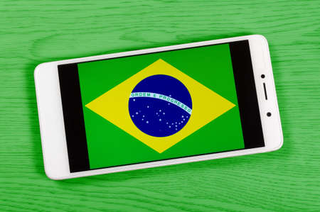 Flag of Brazil composed by placing a smartphone displaying its symbol on a colored wooden background 版權商用圖片