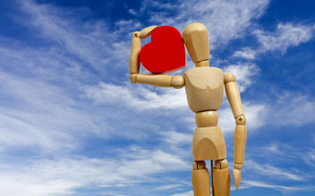 Wooden human mannequin holding a big red heart with a blue sky as a background