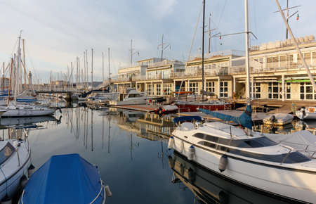TRIESTE, Italy - February 16, 2020: Sacchetta marina in a winter late afternoon, with the historic lanterna beacon in the background