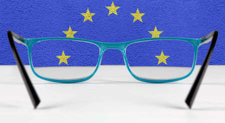 Creative flag of the European Union seen through a pair of eyeglasses lying on a white table
