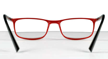 First person view of a pair of red eyeglasses lying on a table over a white background