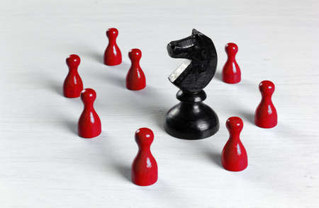 Big black knight chess piece surrounded by smaller red pawns on a white wooden table Stock fotó