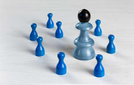 A big pawn with a black head surrounded by smaller pawns on a white wooden table