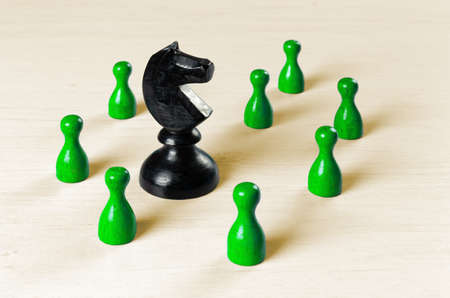 Big black knight chess piece surrounded by smaller green pawns on a white wooden table