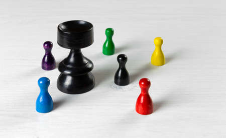 A big black pawn surrounded by smaller pawns on a white wooden table
