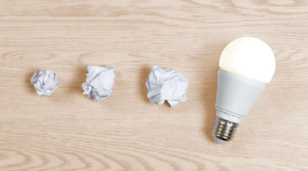 Three crumpled paper sheets and one switched-on lightbulb on a wooden background, to represent the coming to light of the right idea after a few attempts