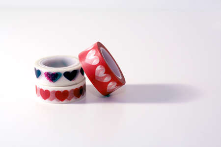 Tape rolls, masking tape rolls in stacks. Red and white tones. white background