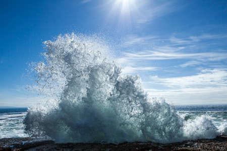 sol radiante: Una ola rompiendo sobre las rocas bajo el sol brillante