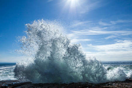 Wave breaking over rocks in the sunshine photo