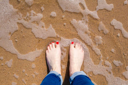 painted toes: View of feet standing in the water on a beach