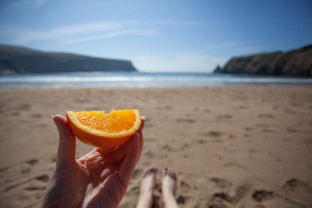 orange peel skin: Hand holding an orange segment on a beach, view of legs and sea
