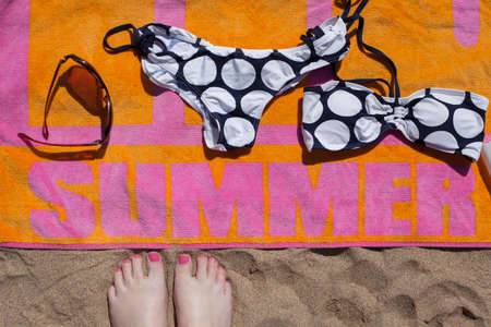 Feet view of colourful beach towel, bikini and sunglasses photo