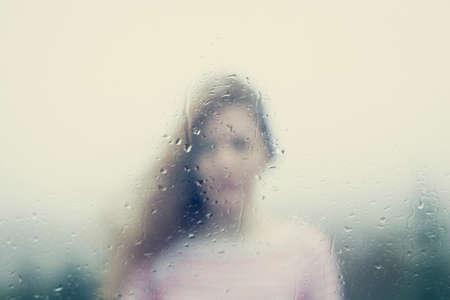 Wazig beeld van een vrouw door een regenachtige venster