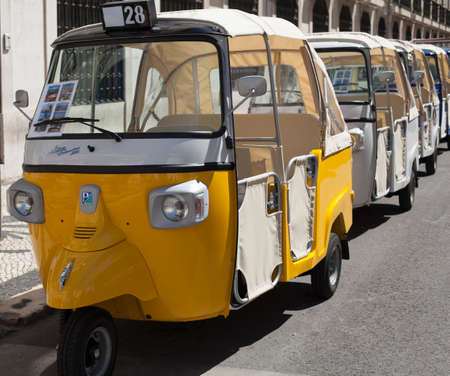 sightseers: A colorful Tuk Tuk in Lisbon, Portugal. Adopted from Thailand and used by tourists and sightseers.
