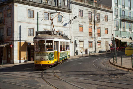 sightsee: Tram 28 carrying people in Lisbon, Portugal.
