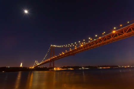 moon gate: The 25th April bridge in Lisbon at night under a full moon. The bridge is a cable- stayed bridge at 2.27km and is very similar to the Golden Gate bridge in San Francisco Stock Photo